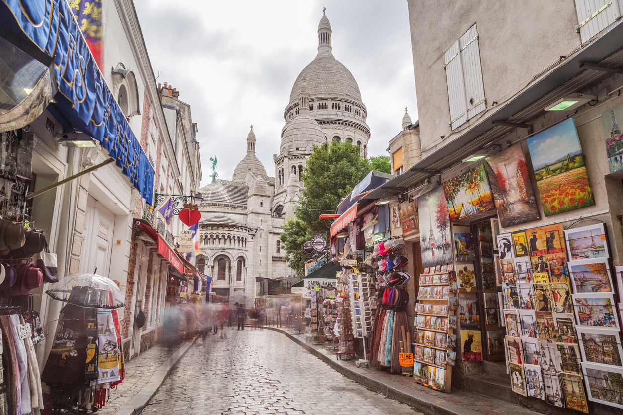 Paris, France - July 28, 2016: A view along streets in Montmartre Paris during the day. The Sacre-Coer and the blur of people can be seen.